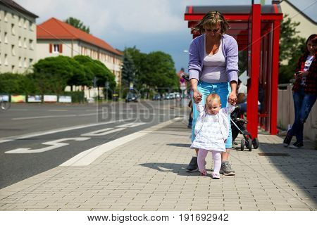 Mom learns to walk a little cute baby at a bus stop, waiting for the bus