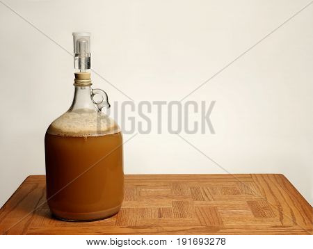 Fermenting Homebrew Beer Isolated on Oak Table