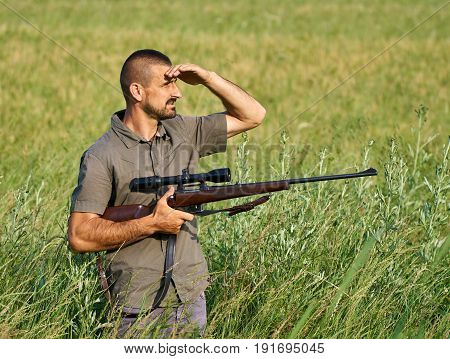 Gamekeeper With A Rifle In A Field