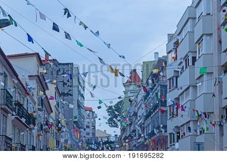 festive city street with decoration of the flags in evening time
