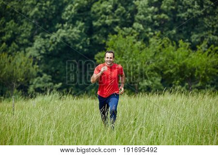 Man Trail Running By The Forest