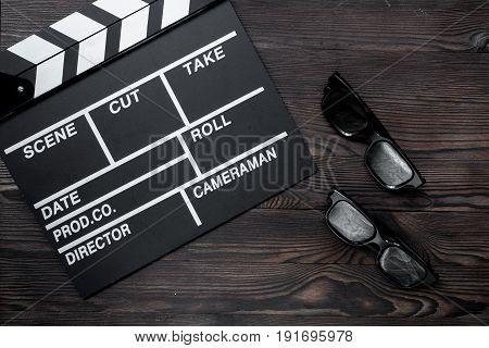 Attributes of film director. Movie clapperboard and sunglasses on wooden table background top view.