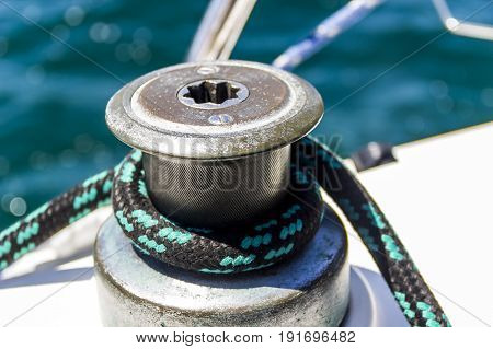 close-up of sailboat winch and black with turquois rope