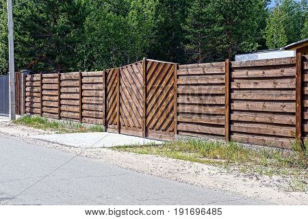 Brown wooden fence with gate near the road