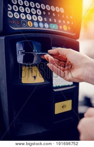 Girl hand inserting ticket into parking machine to pay for parking