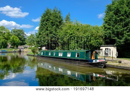 Green canal boat in Birmingham canal at Lapworth
