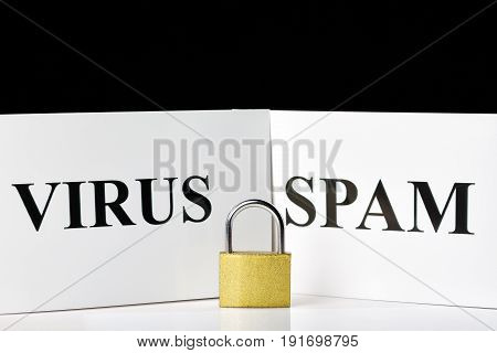 Metal lock near SPAM and VIRUS signs with free space on black background. Internet security concept.
