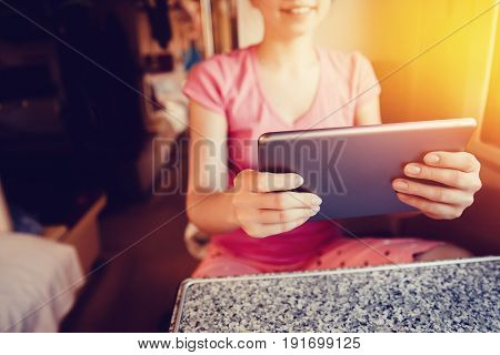 girl is typing text on the tablet computer. The concept of social mobility, the Internet, work as a freelancer.