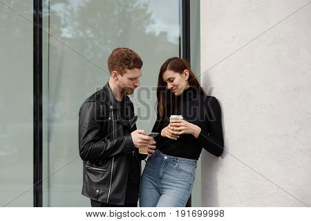 Outdoor shot of young attractive woman flirting with man she gives number phone with shy smile. Handsome guy flirting in the street with pretty girl exchanging phone numbers. Love dating concept