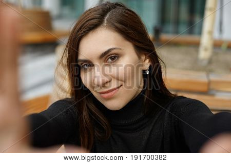 Outdoor portrait of pretty young brunette female taking selfie flirty smiling at camera. Charming girl looking at camera with happy joyful expression and gesturing hands frame. Selective focus on face