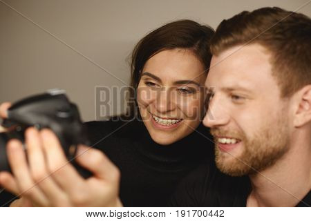 Cropped shot of beautiful smiling Caucasian girl with braces on her teeth with her cheerful boyfriend wearing black clothes looking vacation photos on the camera sitting in cafe. Selective focus
