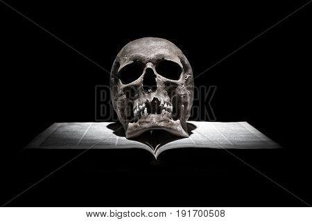 Human skull on old open book on black background under beam of light.