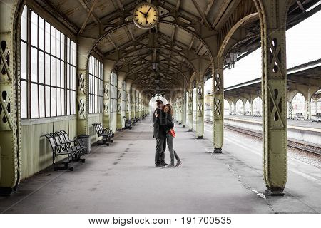 two hipster Lovers hug and kiss on the railway station. People love each other. Man and woman wait for a train for a new trip after hard working days. Travel concept.