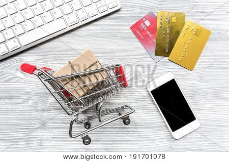 making purchase with phone, credit cards and mini trolley on office desk background top view mockup