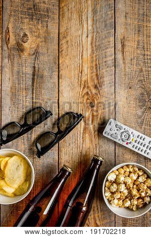 cinema and TV whatching with beer, chips and pop corn on wooden background top view mock-up