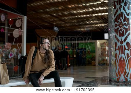 Lonely hipster with long hair sitting in the shopping center and dreaming. An attractive guy in depression. Unhappy and stressed man in swish looks away. Sad guy.