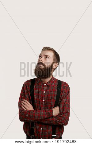 Fashion male blogger with stylish beard like hipster style look up and cross hands across chest. Man in modern red dress shirt with suspenders. Guy wearing casual clothes.