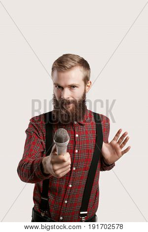 Stylish party maker with microphone look into the camera for an interview on celebration. Modern beard guy in showman. Successful handsome funny journalist isolated on white background.