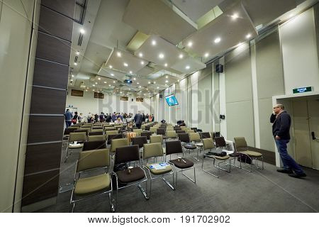 MOSCOW, RUSSIA - APR 25, 2017: Participants have snack at back of auditorium in Novotel Moscow City Hotel during Conference devoted to introduction of artificial intelligence into business.