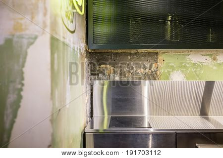 Kitchen in a loft style with shabby walls. There is a chrome steel tabletop with a stove, lockers, dark reticulated shelf, luminous signboard. Closeup. Horizontal.