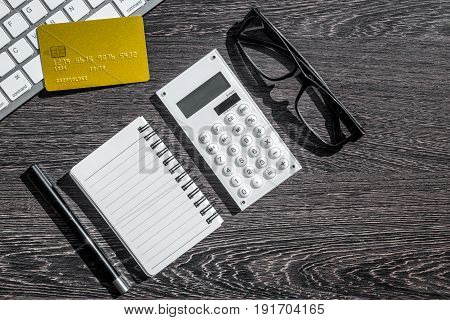 accountant or banker desk with calculator, credit card and keyboard on dark wooden background top view mockup