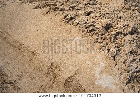 Texture of sand. Industrial sand for construction works. Natural material for bricks and concrete products - loose rock, which contains grains of feldspar, mica, quartz and other minerals.