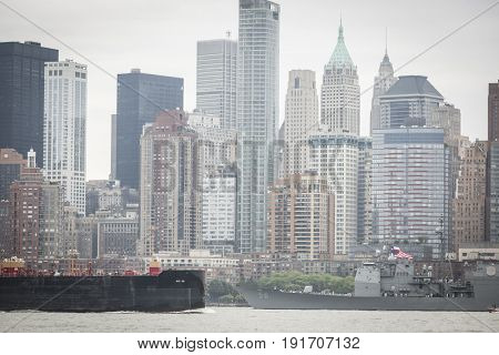 USS San Jacinto (CG 56) passes a barge near Lower Manhattan WTC Financial District on the Hudson River during the Parade of Ships at the start of Fleet Week New York, JERSEY CITY NJ MAY 24 2017.