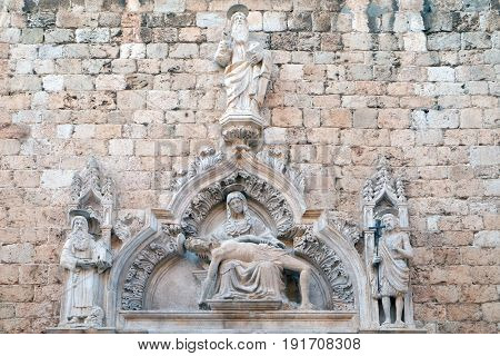 DUBROVNIK, CROATIA - NOVEMBER 29: God the Father, St Jerome, Our Lady of Sorrow and St John the Baptist, portal of the Franciscan church of the Friars Minor in Dubrovnik, Croatia on November 29, 2015.