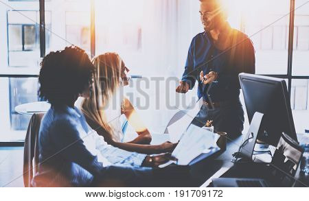 Young team of coworkers making great meeting discussion in modern coworking office.Hispanic businessman talking with two business womans.Teamwork concept.Horizontal, blurred background, flares effect