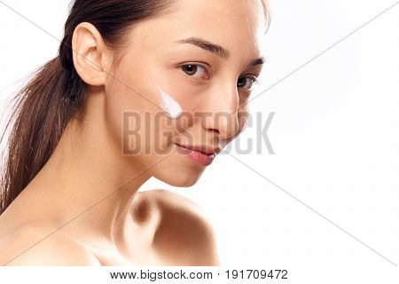 Woman with cream on face on isolated background.