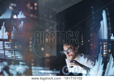 Concept of digital diagram, graph interfaces, virtual screen, connections icon.Young finance analist working at modern office.Man using contemporary laptop at night, blurred background.Horizontal