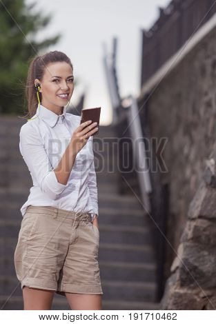Youth Concepts and Ideas. Stylish Modern Caucasian Brunette Woman Posing Outdoors With Smartphone Gadget and Wearing Wireless Headphones. Vertical Image Orientation