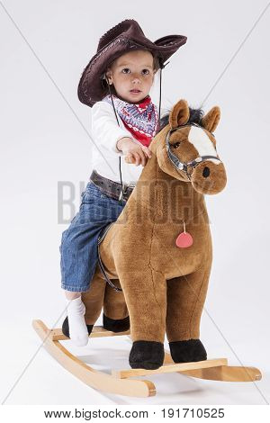 Children Concepts. Little Caucasian Girl Posing in Cowgirl Clothing with Toy Horse Against White Background. Vertical Image