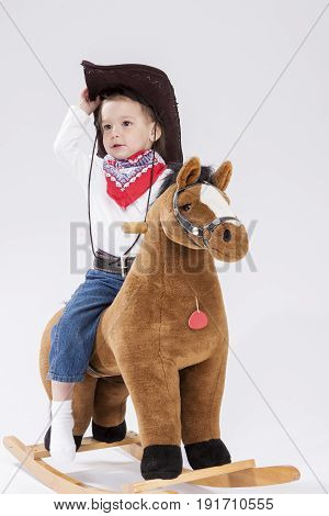 Little Children Consepts. Little Caucasian Girl in Cowgirl Clothing Posing On Symbolic Horse Against White. Holding Her Statson. Vertical Image