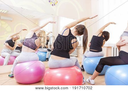 Sport Fitness Wellness and Helathy Lifestyle Concepts. Group of Five Caucasian Female Athletes Having Stretching Exercises with Fitballs Indoors.Horizontal Image Composition