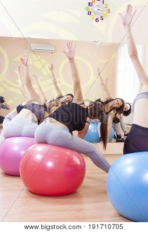 Sport Fitness Helathy Lifestyle Concepts. Group of Five Caucasian Female Athletes Having Stretching Exercises with Fitballs Indoors. Vertical Image Composition