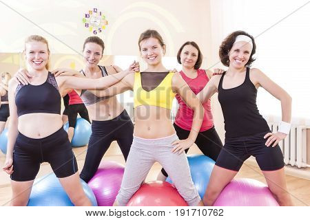 Sport and Healthy Lifestyle Concepts. Group of Five Happy Caucasian Female Athletes Posing Together Embraced Against Fitballs in Gym.Horizontal Image