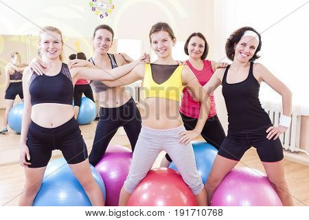 Sport and Healthy Lifestyle Concepts. Group of Five Happy Caucasian Female Athletes Posing Together Embraced Against Fitballs in Gym.Horizontal Image Composition