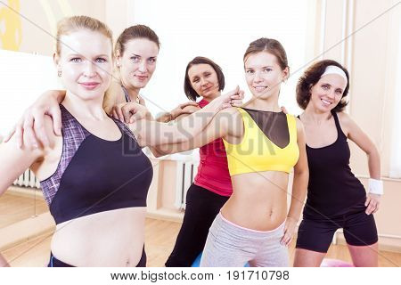 Sport and Healthy Lifestyle Concepts. Closeup Portrait of Five Happy Caucasian Female Athletes Posing Together Embraced Against Fitballs in Gym.Horizontal Image Orientation