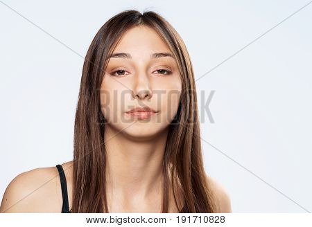 Serious woman with flowing hair, woman on a light background portrait.