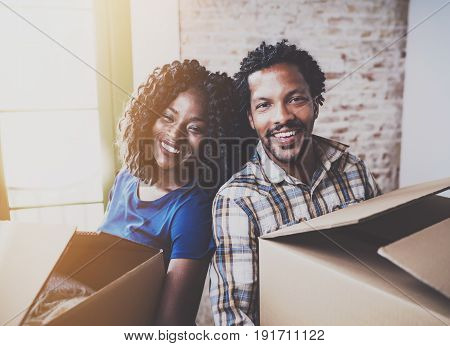 Happy young black african couple moving boxes into new home together and making a successful life.Cheerful family sitting in empty new apartment.Horizontal.Blurred background.Cropped.Flares