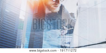 Businessman working process at modern office.Young coworker working at the wooden table with laptop computer.Double exposure, skyscraper building blurred background.Horizontal wide.Flares effect.