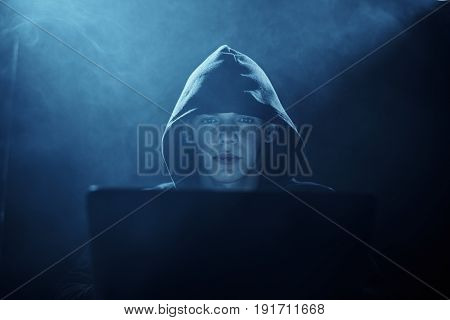 Hacker hacks computer networks, a hacker on a dark background.