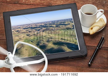 Nebraska Sandhills near Thedford in spring scenery - reviewing aerial picture on a digital tablet with coffee and drone
