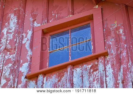 A glass window with panes in a red barn