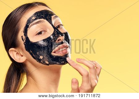 Woman put on cosmetic mask on yellow background.