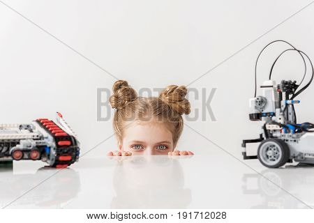 Interested girl is hiding behind table and looking at camera with expectation. Robots are on countertop. Close up