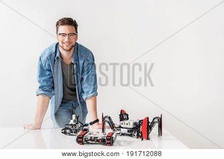Happy man is looking at camera with bright smile. He standing near desk with robot model. Portrait
