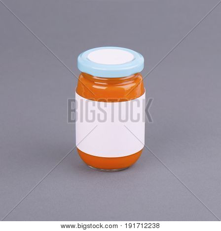 Orange glass jar for baby food bank on grey background. Organic baby food puree. Mock up without template design label. Photo