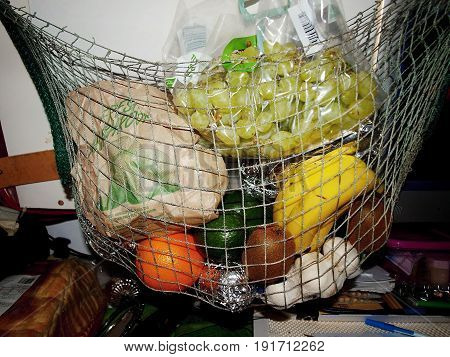 A mixed bag of colourful fruit hanging in a string basket. fruit basket string string bag. hanging basket grapes bananna orange kiwi fruit avacardo garlic